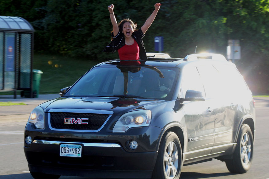 Senior Amy Manzano-Foote stands up through a car sun roof while yelling