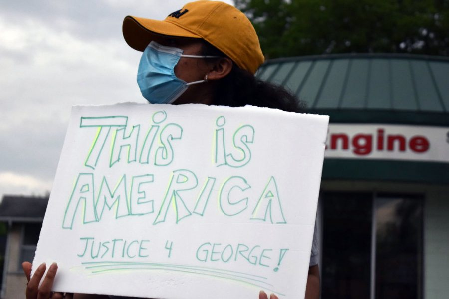 "A protester holds a sign with the words ""This is America, justice 4 George."" There were many chants used throughout the protest including ""I can't breathe"" and ""say his name, George Floyd."""