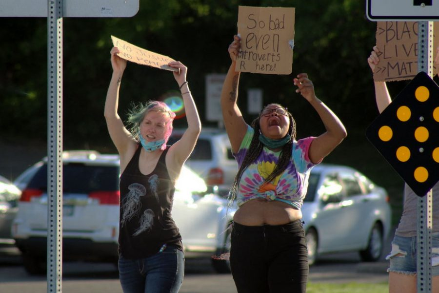 Two people chant during the event while standing on the median. Throughout the memorial they held signs up saying