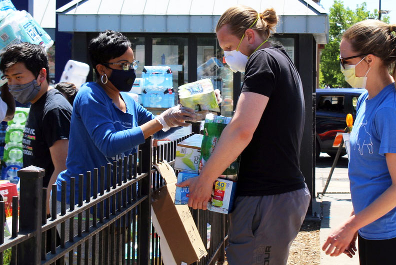 A man donates non-perishable items for community members affected by store closures in Minneapolis. A Minneapolis school, Sanford Middle School, as well as many other local churches and schools, were accepting donations.
