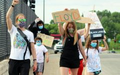 """A group of protesters June 4 walk across a bridge on Louisiana Ave. holding signs that say """"Floyd"""" and """"Black Lives Matter."""" Protesters gathered for the """"SLP: Honoring George Floyd - peaceful/socially distant gathering"""" at the pedestrian bridge on Wayzata Blvd between Winnetka and Louisiana and the Louisiana Ave. bridge."""