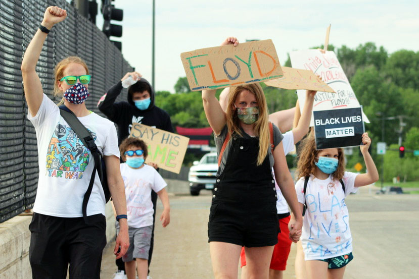 "A group of protesters June 4 walk across a bridge on Louisiana Ave. holding signs that say ""Floyd"" and ""Black Lives Matter."" Protesters gathered for the ""SLP: Honoring George Floyd - peaceful/socially distant gathering"" at the pedestrian bridge on Wayzata Blvd between Winnetka and Louisiana and the Louisiana Ave. bridge."