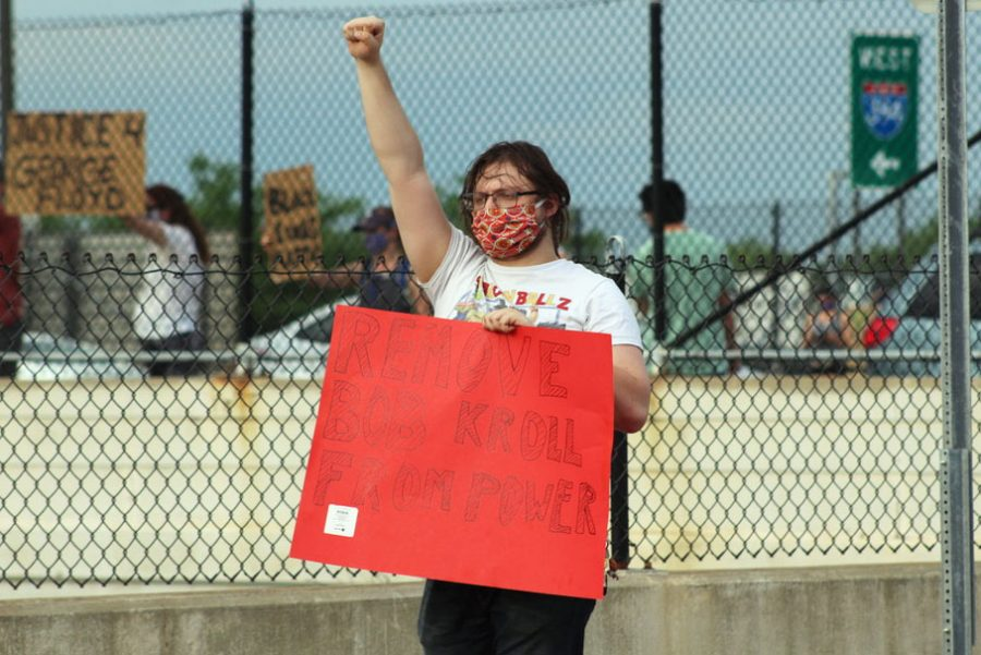 """An attendee holds her her fist up while holding a sign that reads """"remove Bob Kroll from power."""" The gathering was originally scheduled for June 2, however the event was rained out."""