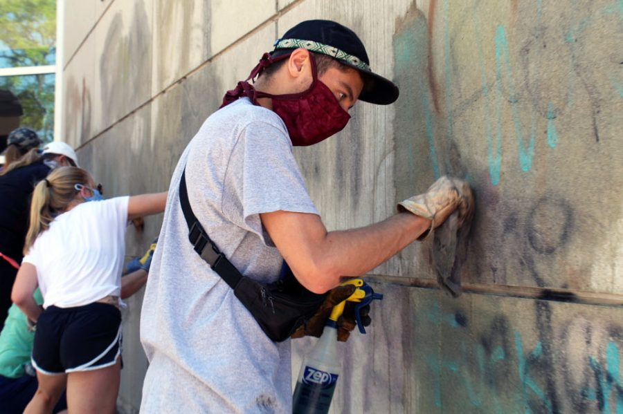 """A volunteer helps clean graffiti off of the East Lake Hennepin County Library. Some graffiti on the library included phrases such as """"No justice, no peace."""""""