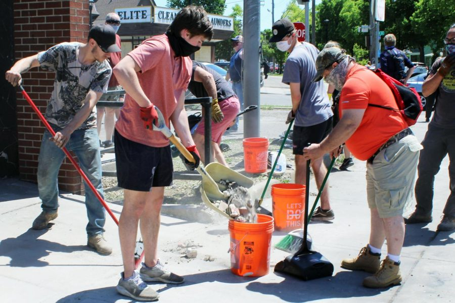Clean-up volunteers shovel debris from Minnehaha Post Office into buckets. Rioters burned the post office, causing extreme damage May 29.