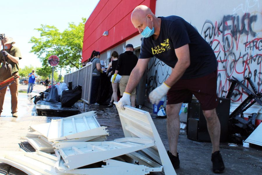 A volunteer adds garbage to a pile at the Lake Street Target. That location of the Minnesota-based department store was looted and damaged May 28.