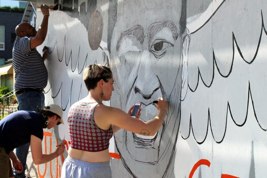 Artists paint a mural of George Floyd May 31 on Lake Street. Murals are being created worldwide to honor Floyd and call for change.