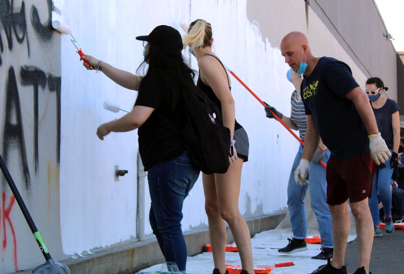 In order to cover up graffiti, volunteers help repaint the exterior walls of the Lake Street Target. Other volunteers worked inside the Target, clearing out trash and flood water.