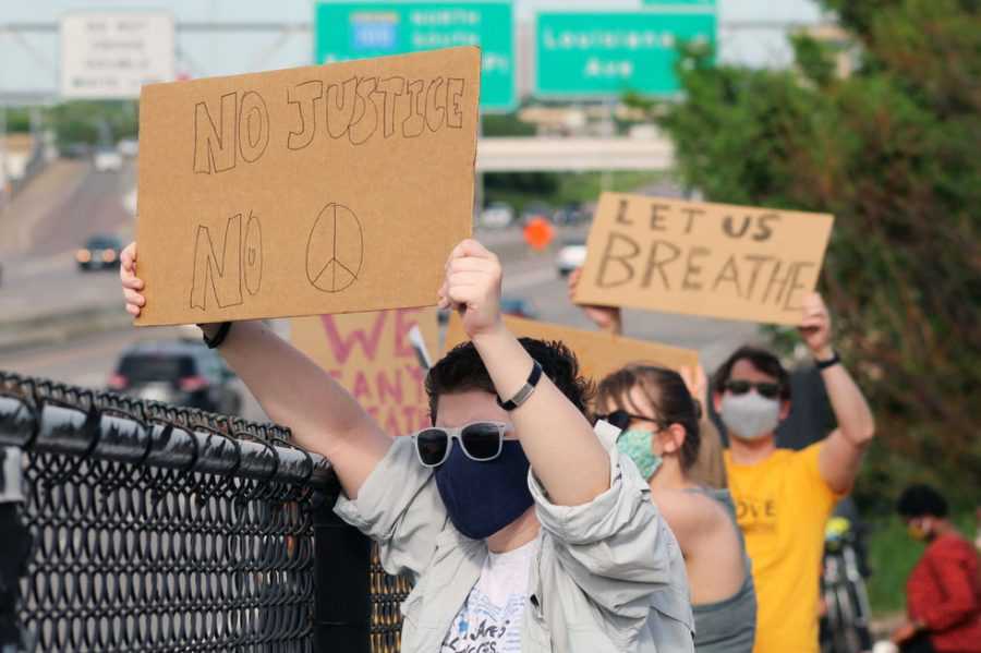 A protester holds a sign above the highway for people driving by to see. Cars on Highway 100 honked as they drove by.