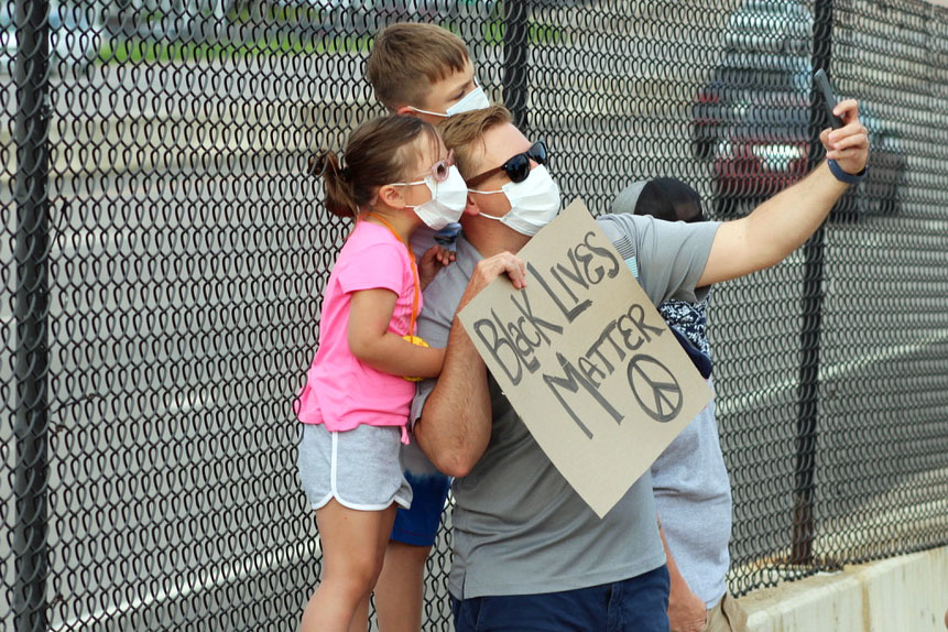 """A family takes a selfie while holding a sign that reads """"Black Lives Matter."""" The pedestrian bridge on Wayzata Boulevard between Winnetka & Louisiana Avenue was reserved for families."""