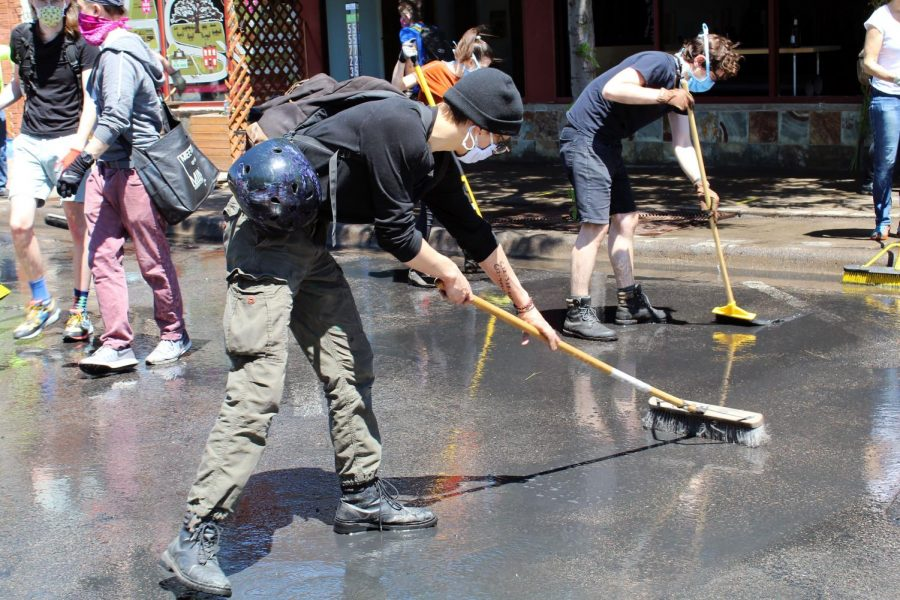 Volunteers clean the streets with brooms. Following multiple nights of protests and riots, many streets were lined with ashes.