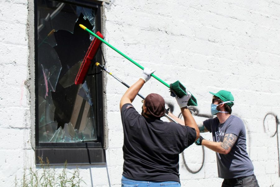 Volunteers clean out the shards of glass from a broken window. Businesses along Lake Street had varying levels of damage, ranging from minor graffiti to extreme fire damage.
