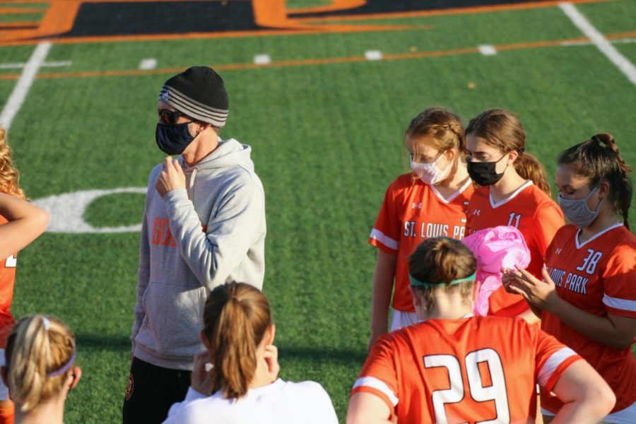 The girls' varsity soccer team holds a strategic meeting during their halftime break Sept. 30. While not playing, the MSHSL has suggested to wear masks in order to prevent the spread of COVID-19 this season.