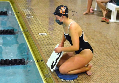 Senior Maddy Doherty helps her teammate out during the JV 500 freestyle race by putting signs into the water Sept. 15. The signs let the swimmer know how many laps they have completed.