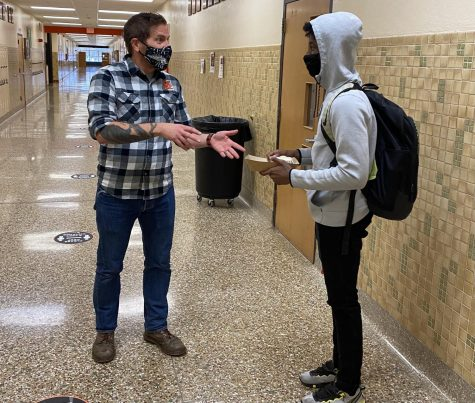Science teacher Patrick Hartman helps a student in the hallway. Helping a student in the hallway during freshman orientation was one of the challenges featured in Employee Relief.