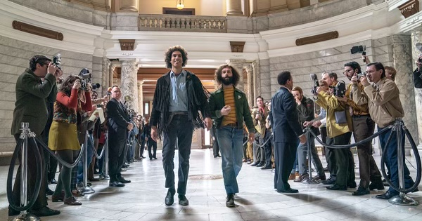 Fair use from Netflix. Abbie Hoffman (Sacha Baron Cohen) and Jerry Rubin (Jeremy Strong) being photographed by many photographers while walking towards the court room for their trial. The movie is based on events from the 1969 political trial.