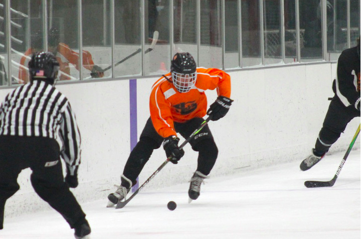 Junior Juan Russy keeps the puck under control while trying to score against Osseo. Boys' hockey was down three players due to COVID-19 exposure.
