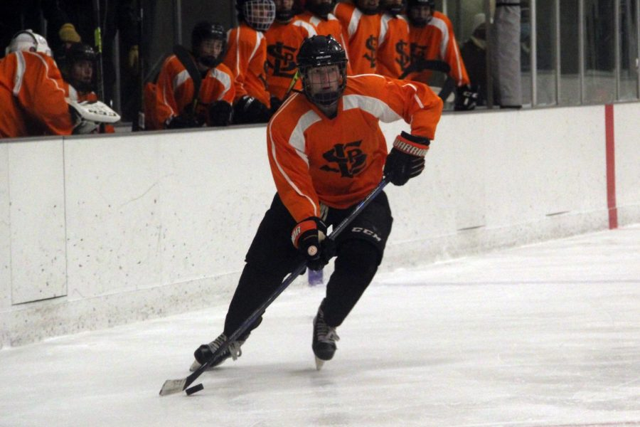 Senior Davis Bye carries the puck up the ice during the boys' varsity hockey game against Osseo Nov. 12. Bye plays as a defenseman and has played hockey since the age of four.