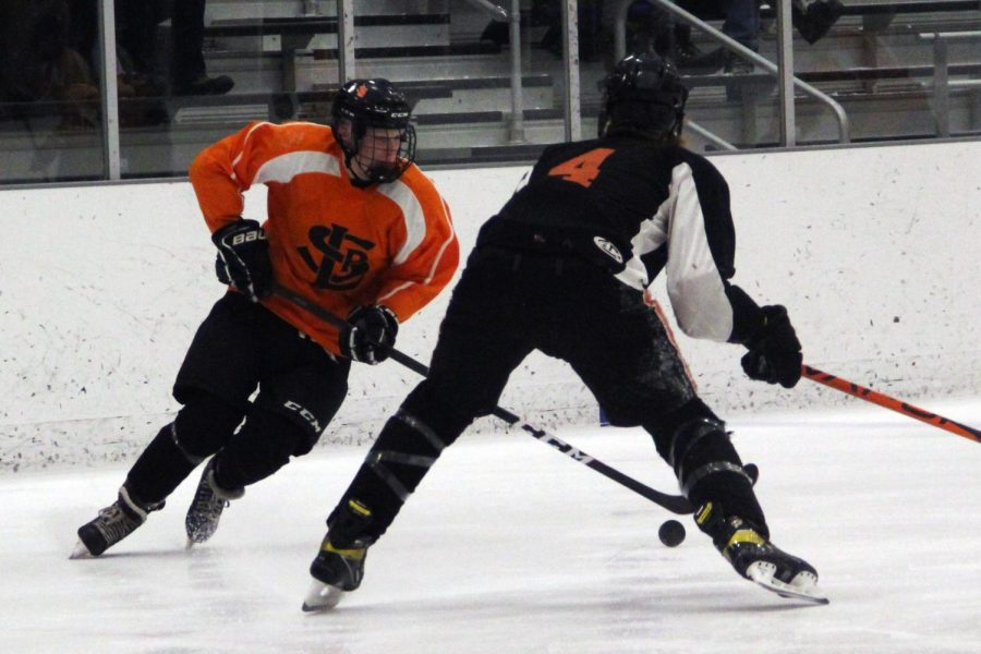 Junior Ben Farley battles for control of the puck against Osseos player. Farley scored the first goal in the first period.