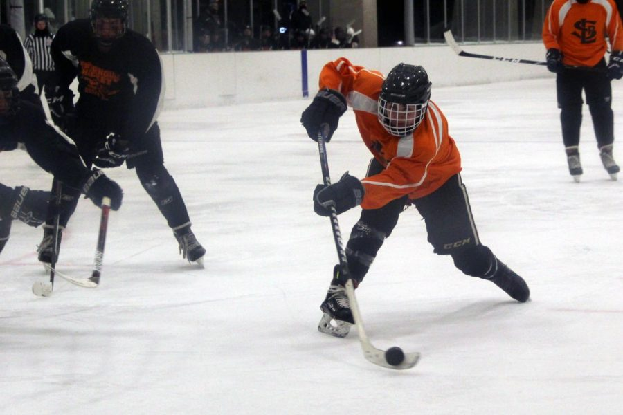 Senior Lucas Hand prepares to take a shot while Osseo defenders block the goal. Hand scored the third goal in the second period.