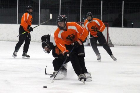Senior Davis Bye protects the puck from Osseo's defenders Nov. 12. Governor Tim Walz new restrictions on high school sports have delayed them for four weeks.
