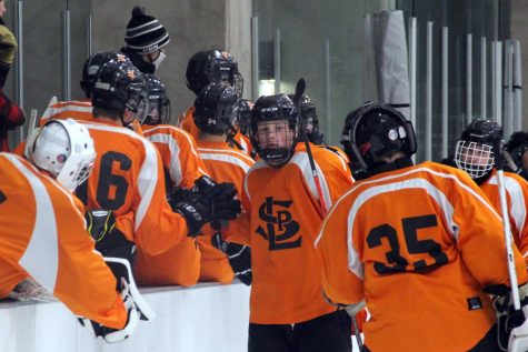 Junior Ben Farley high-fives his teammates after a goal was scored Nov. 12. Boys' hockey is one of many sports that has been down players due to COVID-19 exposure.