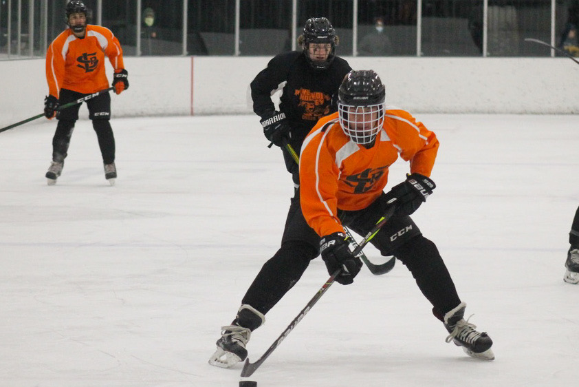 Junior Juan Russy skates up the ice with the puck in his possession Nov. 12. After Gov. Tim Walz's restrictions end, students believe high-risk sports like hockey may be delayed longer than low-risk sports such as Nordic skiing