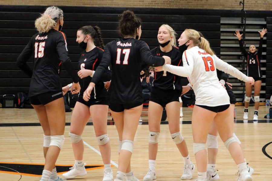 Volleyball players celebrate after scoring a point Nov. 12. All athletes must wear facial coverings when games return Jan. 14.