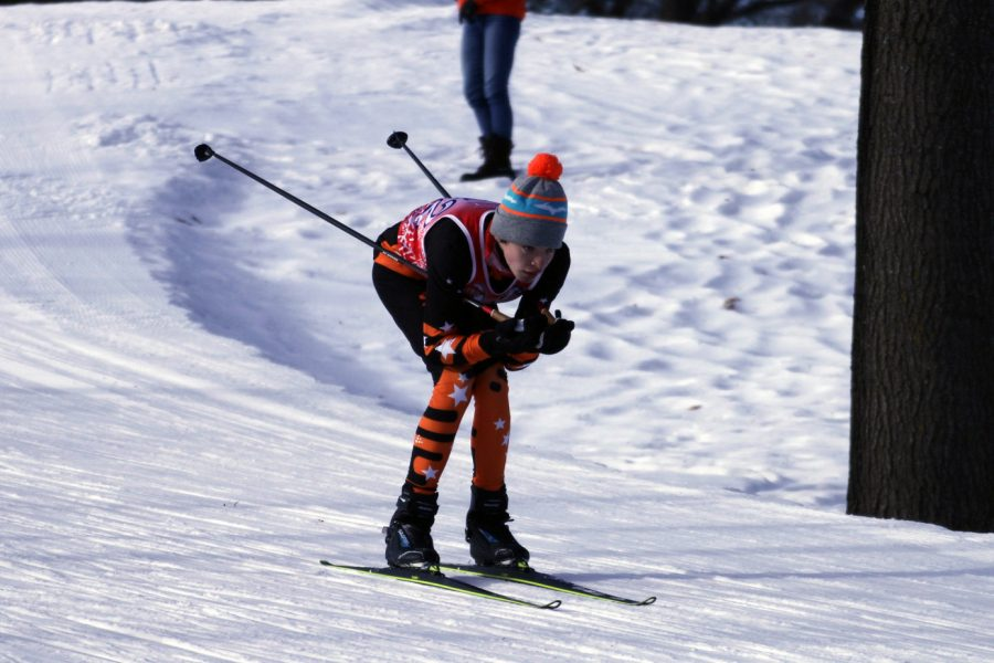 Freshman Thomas Shope skis down a hill Jan. 21. Skiers use hats to show individuality during races as they all are required to wear the team uniform.