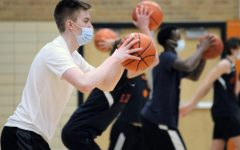 Junior Blake Anderson passes the ball during boys' basketball tryouts Jan. 4. Masks must be worn at all times including during games.