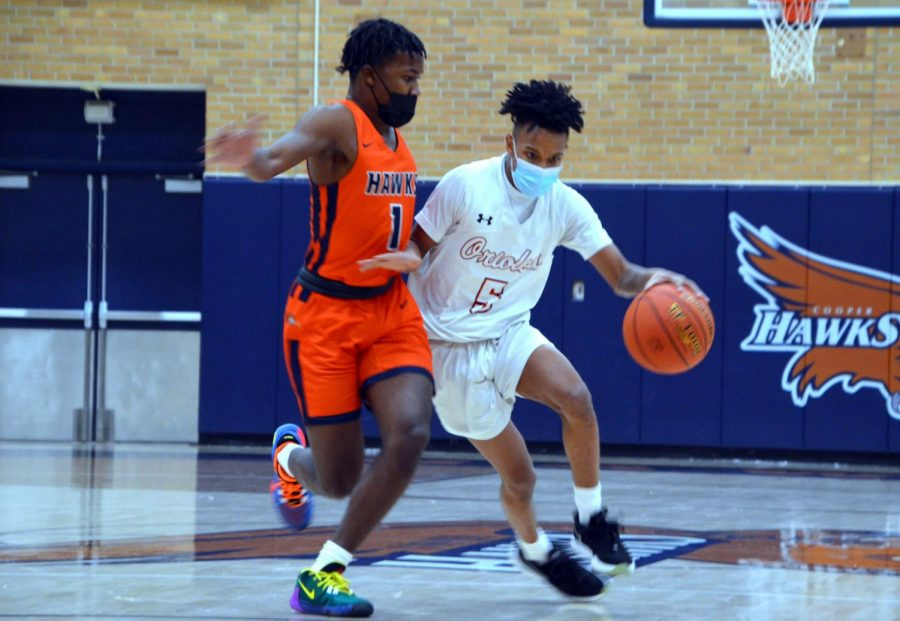 Senior Tyshawn Lyons dribbles towards the hoop for a contested layup Jan. 21. Park lost to Cooper 78-61 in a hard fought game.