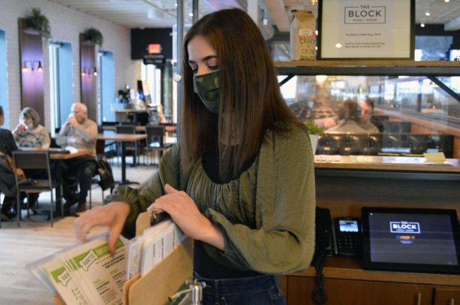 Senior Claire Diamon-Wheeler organizes menus at The Block Jan. 15. The Block is now open for indoor dining, and takeout.