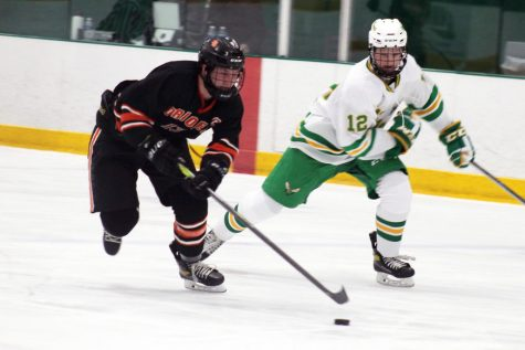 Senior Jack Wandmacher tries to skate pass Edina's senior defenseman Owen Davis. Park tied 4-4 with Edina.