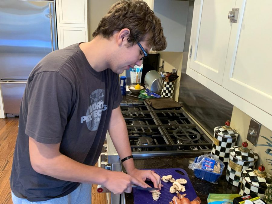Photo illustration by Jacob Khabie. Junior Tobias Khabie chops up mushrooms at his home Jan. 21. Khabie has taken up cooking to keep himself busy at home.