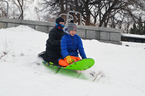 Fifth-grader Judah Lissauer and eighth-grader Ari Lissauer sled down a hill on Cedar Lake Jan. 16. Sledding is one of many winter activities students are using to stay entertained during COVID-19.