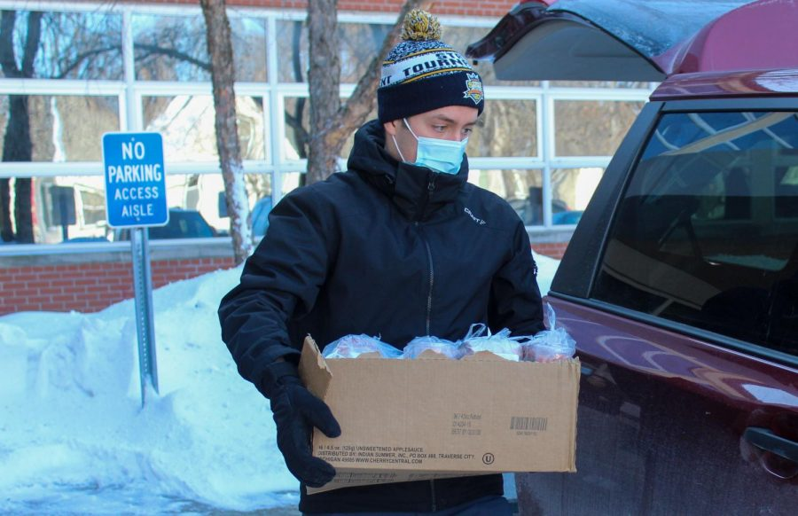Senior Danny Walsh carries federally funded meals to his car to be donated. Walsh will be donating unneeded meals twice a week for the rest of the year.