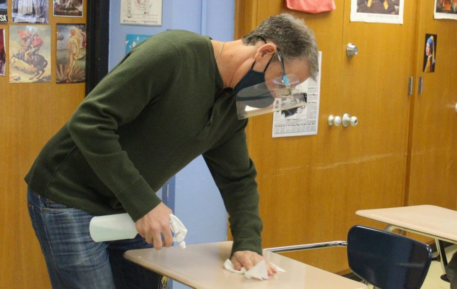 Jeffrey Cohen wipes down desks during an in-person class Feb. 26. Teachers are told to wipe down all desks after each class.