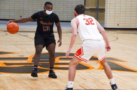 Senior Jordan Moore dribbles down the court in a game against Benilde Feb. 5. Athletes struggling in classes will now be required to attend tutoring on Wednesdays.