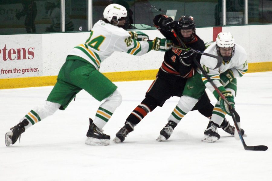 Junior Ben Farley fights off two Edina players. Farley scored two goals throughout the 2020-21 season.
