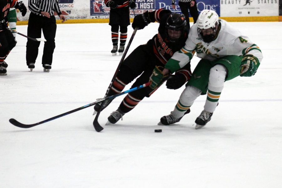 Jack Wandmacher pushes his way to win the puck. The first period of the game ended 1-1.