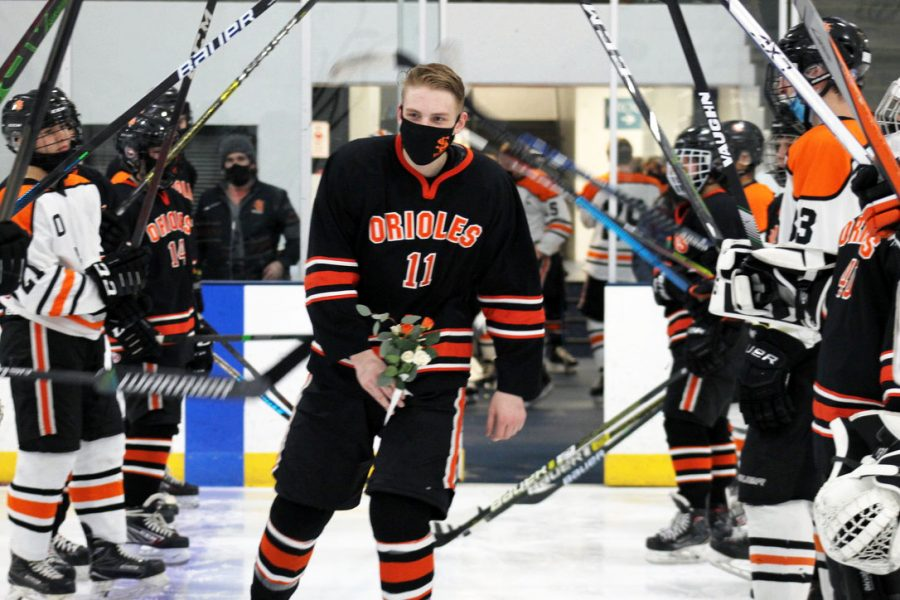 Senior Cameron Donahue skates through the tunnel of hockey players to meet his parents for Senior Night March 13. Due to COVID-19, boys' hockey did not have a scheduled game and Park held small, inter-squad scrimmages.