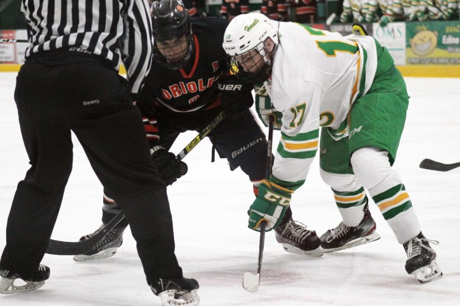 Junior assistant captain Stanley Regguinti faces off for the puck with an Edina hockey player. Park lost 5-2 to Edina.