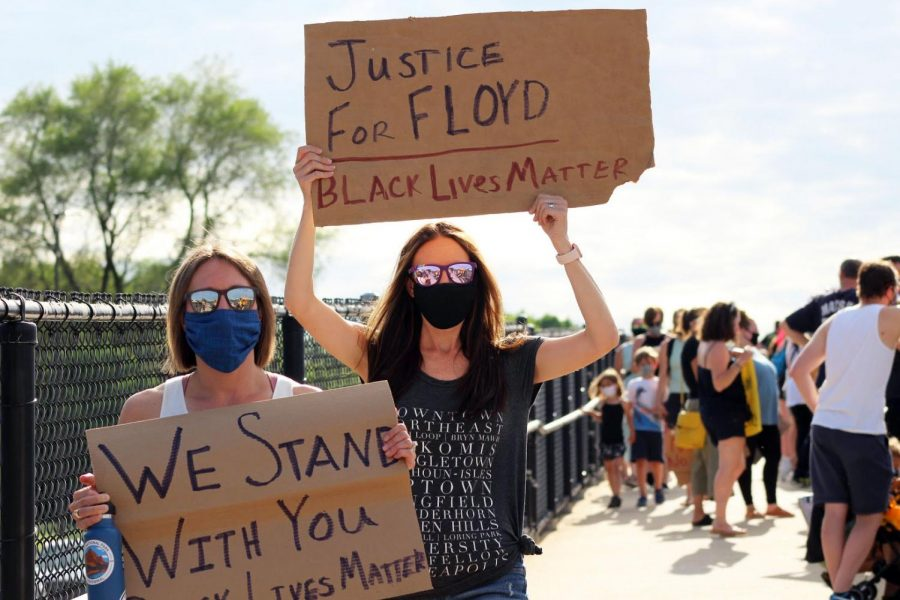 Protesters hold signs on a bridge during a family-friendly protest June 3. St. Louis Park leaders are considering amending or repealing an ordinance banning targeted residential protests.