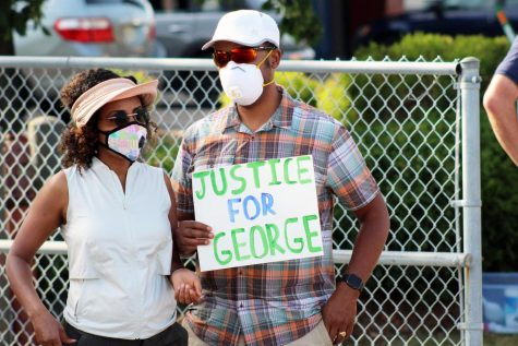"Protesters hold up a ""justice for George"" sign at a protest June 4. Former police officer Derek Chauvin is being charged for the murder of St. Louis Park resident George Floyd."