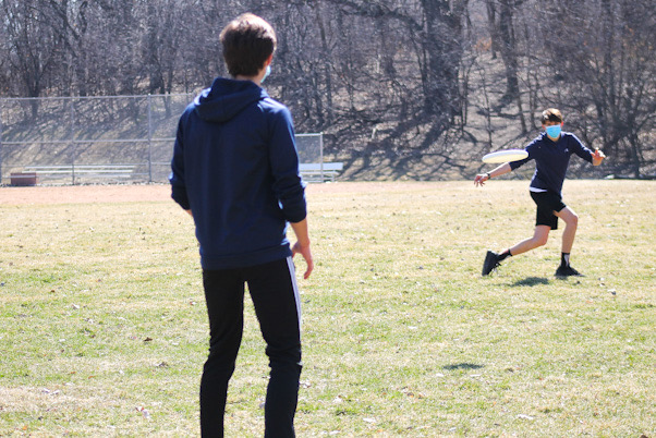Freshman Thomas Shope passes a frisbee during practice at Minikahda Vista park is approved.