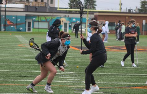 Seventh grader Gretchen Fandel Thompson faces defender freshman Ruby Smith during practice April 12. The lacrosse team has begun practices preparing for their spring season.