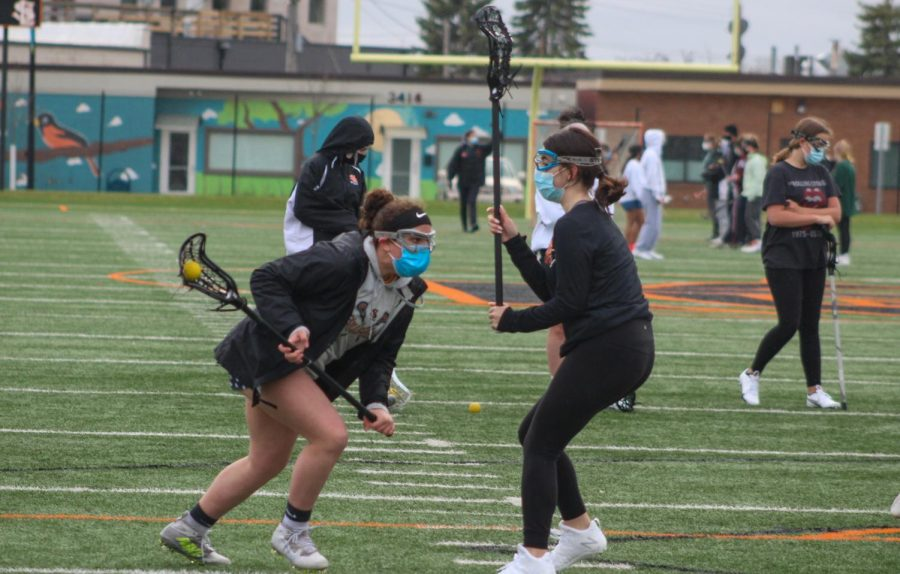 Seventh grader Gretchen Fandel Thompson faces defender freshman Ruby during practice April 12. The lacrosse team has begun practices preparing for their spring season.