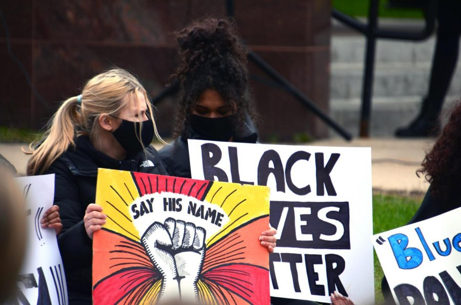Juniors Lili Jampsa and Symone Morrison hold signs to show their support during the walkout April 19. Students supported the walkout by wearing all black.