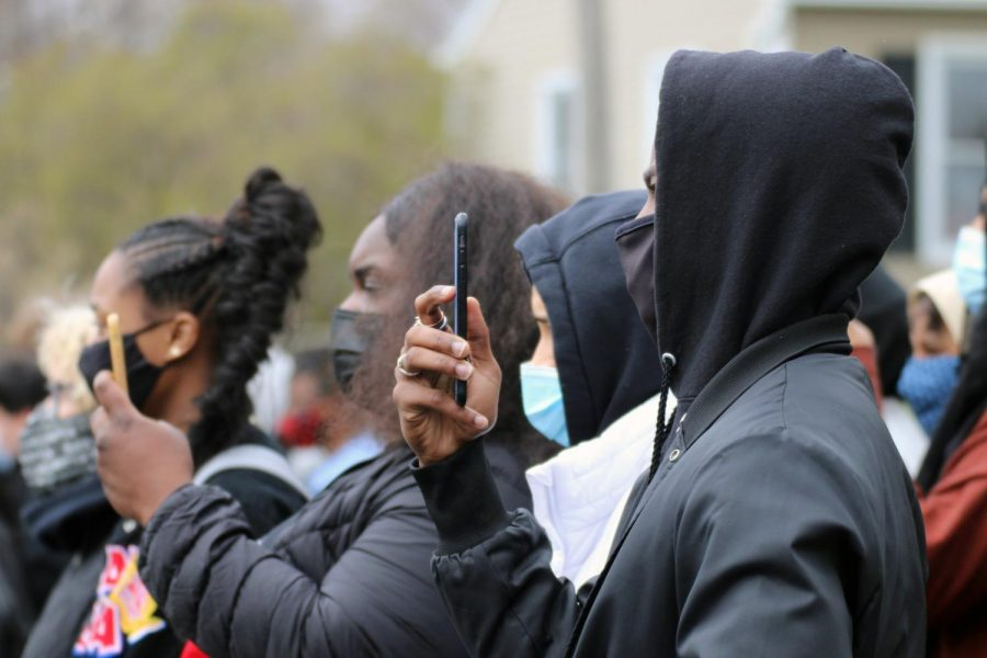 Senior Roselyne Iwundu takes photos and videos of student activists during the protest April 19. Many students and staff participated in the walkout to show solidarity with the movement.