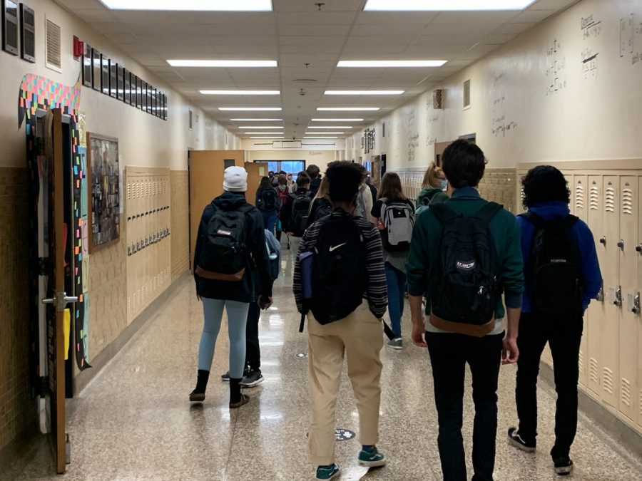 Students walking through the hallway to get to class on April 9. while COVID-19 cases rise, students feel conflicted going back to 100%.